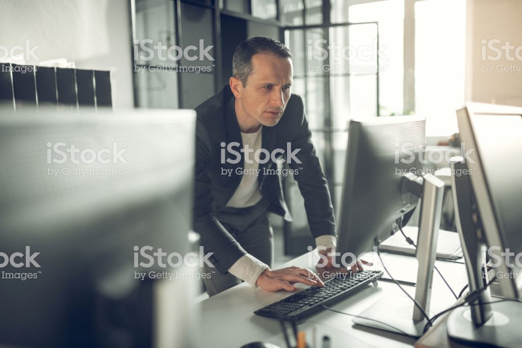 Handsome businessman. Handsome prosperous businessman typing e-mail for business partner while using computer
